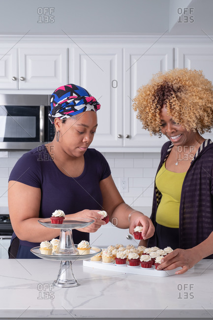 Black mother and daughter arranging fresh baked cupcakes on a glass stand in kitchen