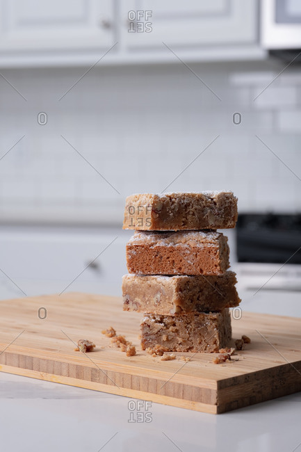 Stack of blondies on cutting board in kitchen