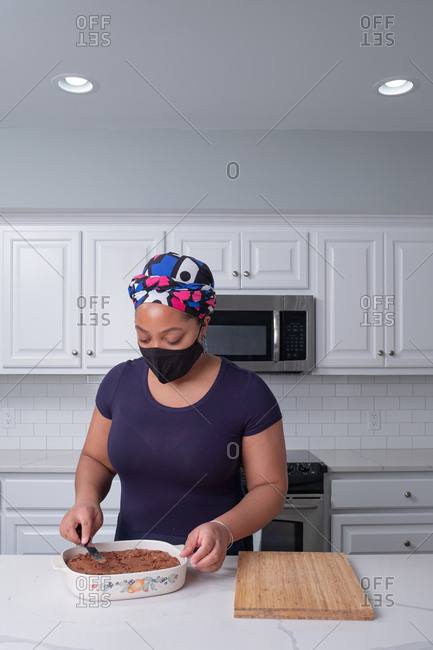 Beautiful black woman baking in kitchen at home
