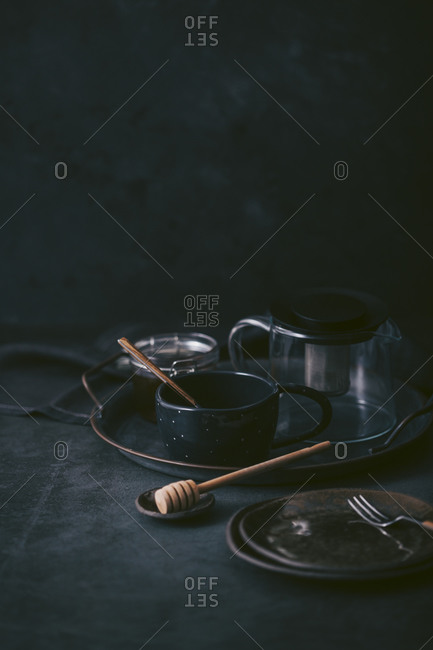 Dark plates and mug with coffee carafe on tray in front of dark background