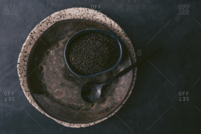 Coffee grounds in a bowl on rustic plates and dark background