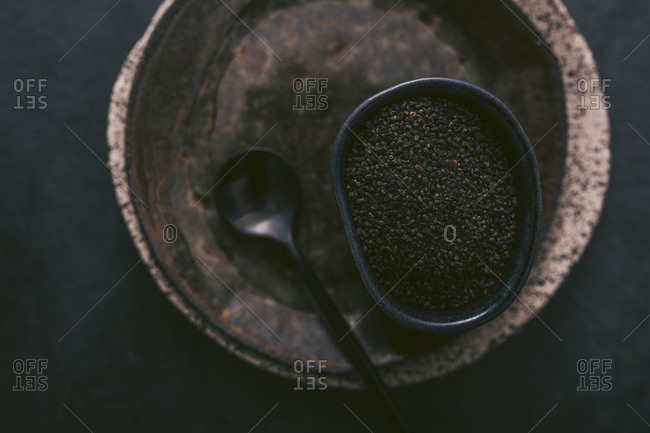 Top view of coffee grounds in a bowl on rustic plates and dark background