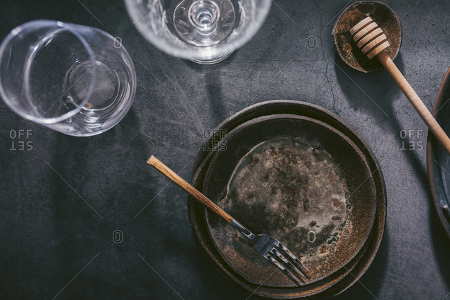 Glasses and rustic plates on dark background