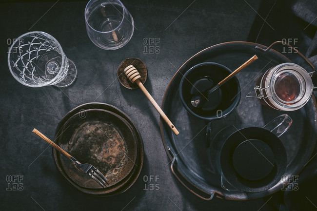 Top view of rustic plates and cups with coffee carafe and honey on tray on dark background