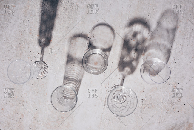 Overhead view of glasses and shadows on light surface