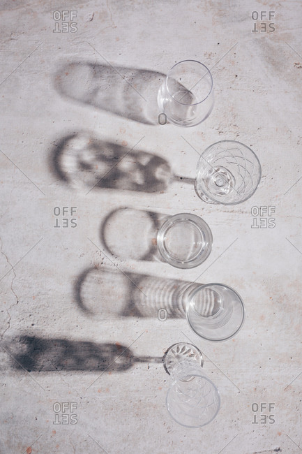 Top view of glasses and shadows on light surface