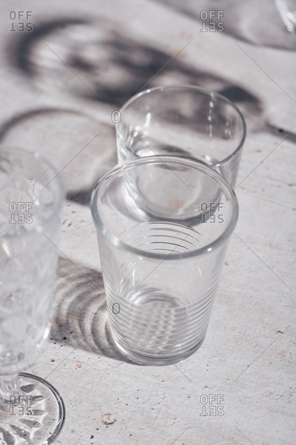 Drinking glasses and shadows on light surface