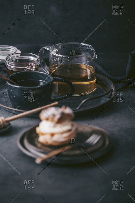 Tea on a tray with honey served beside a pastry on dark surface
