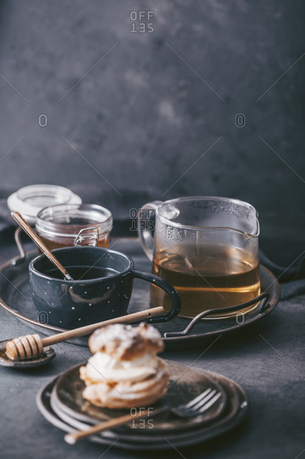 Tea carafe with honey on a tray served beside a pastry on dark surface