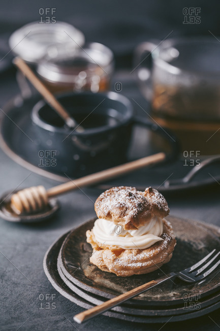 Close up of a pastry with cream filling and tea in the background