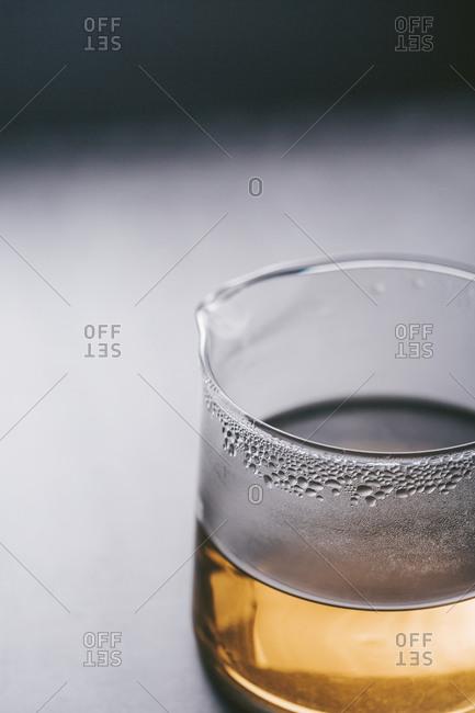 Tea carafe with condensation on dark surface