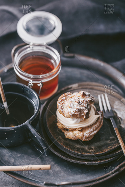 Pastry with cream filling served on a rustic tray with tea and honey