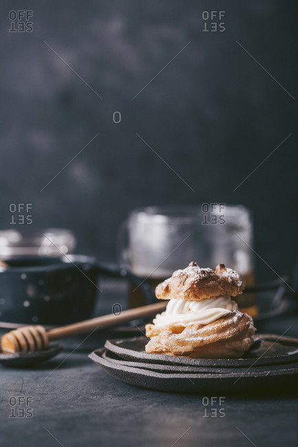 Flaky pastry with cream filling served on rustic dish with tea in background