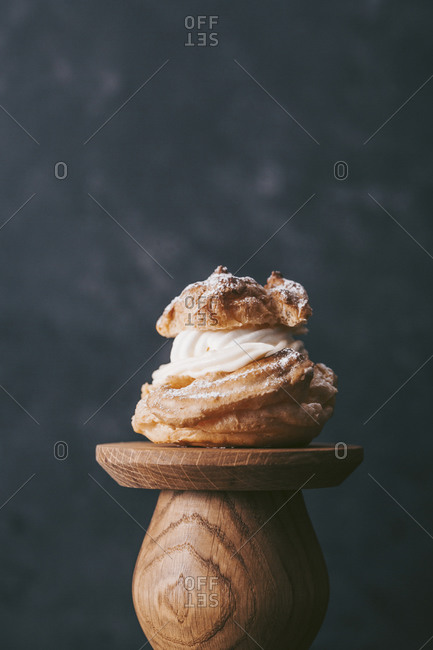 Close up of a cream filled pastry on wooden pedestal