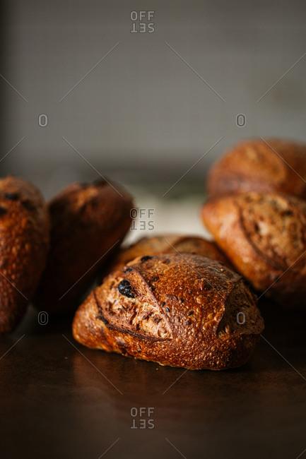 Pile of fresh bake bread loaves on wooden surface with copy space