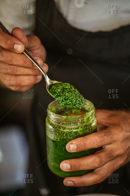 Chef holding a jar and spoon with fresh made pesto