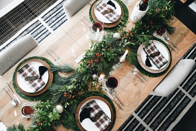 Top view of a table set with classic holiday decor and place settings