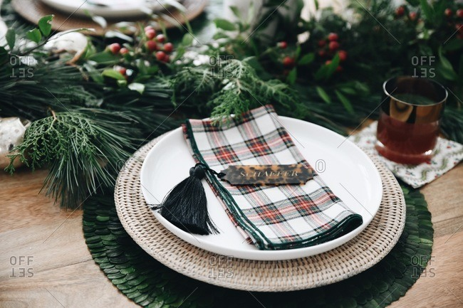 Close up of a place setting on a table set with classic holiday decor