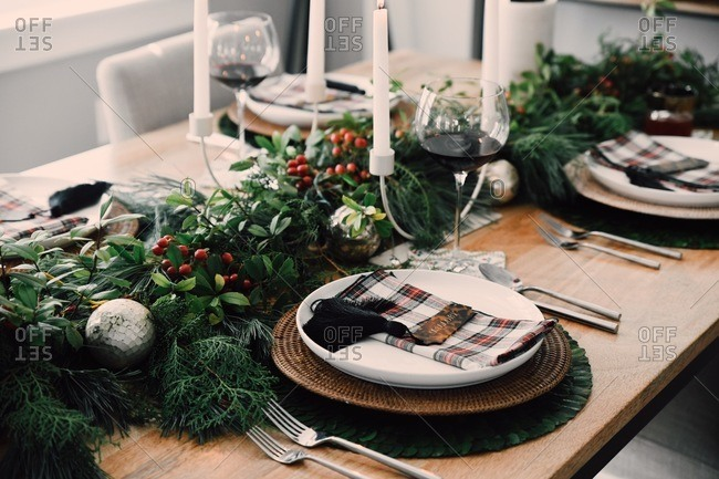 Table set with classic holiday decor and place settings with wine