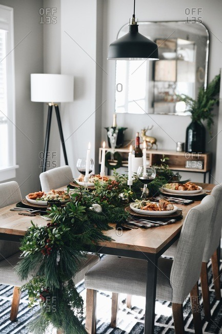 A small Christmas gathering dinner table set and served with food