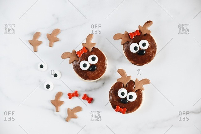 Adorable reindeer Christmas sugar cookies on a white marble surface