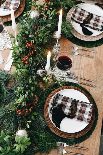 A holiday gathering table set with red wine and lit candles viewed from above