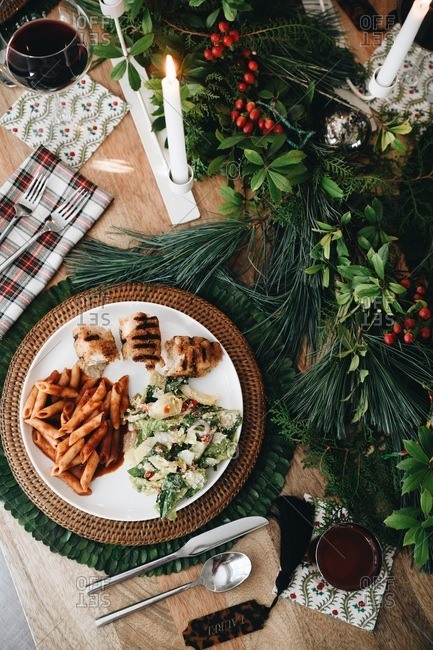 Overhead view of food on a dinner table set for a small Christmas gathering