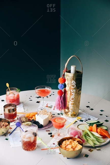 Appetizers and cocktails on a table with confetti at a party