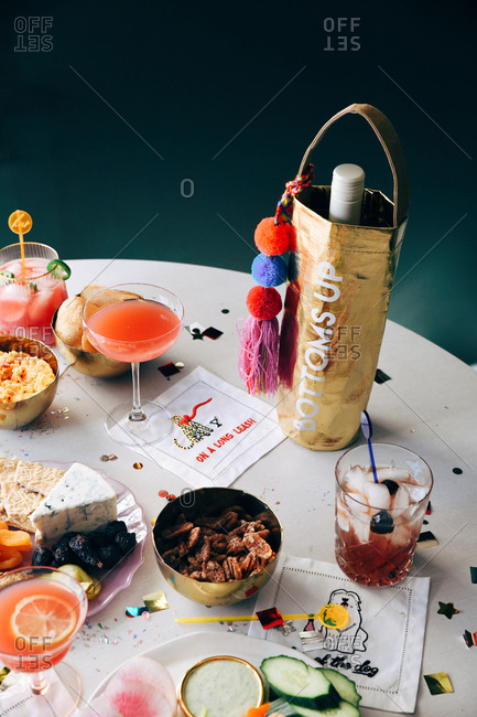Snacks and cocktails on a table with confetti at a party