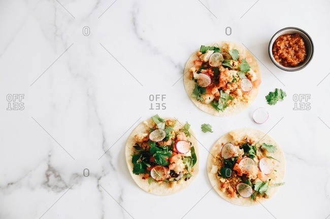 Top view of three cauliflower tacos on white marble surface