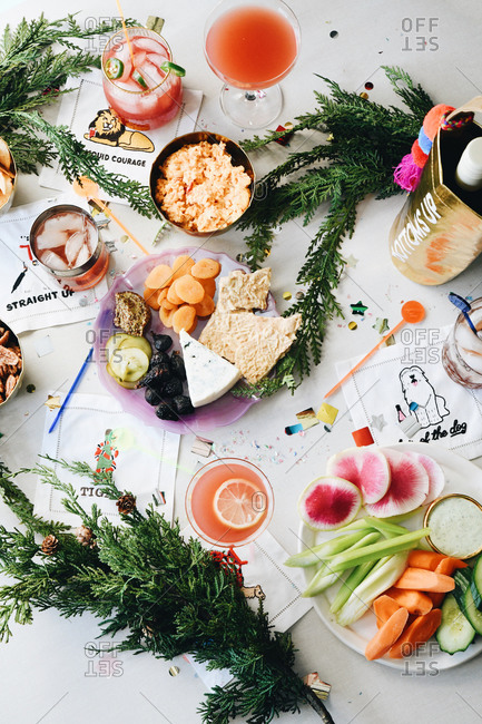 Alcoholic beverages and appetizers on a party table with confetti