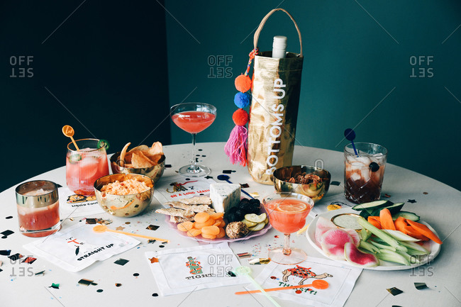 Cocktails and snacks on a table with confetti at a New Year's Eve party
