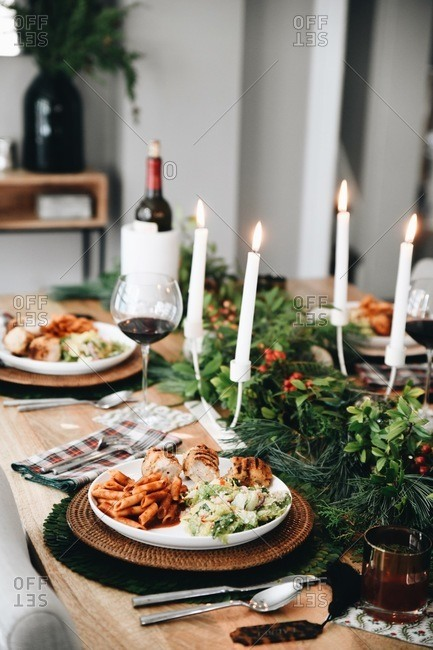 Food served on a dinner table set for a small holiday party with candles and wine