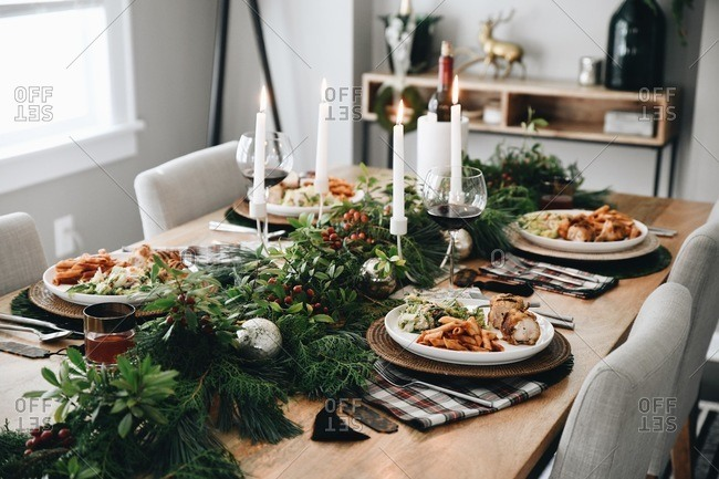 Festive dinner table set for a small holiday party with candles, food and wine
