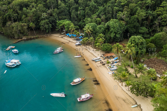 Aerial View Of Boats Anchored In Blue Water Along Tropical Island Beachfront Of A Paraty Fishing Village, Rio De Janeiro, Brazil