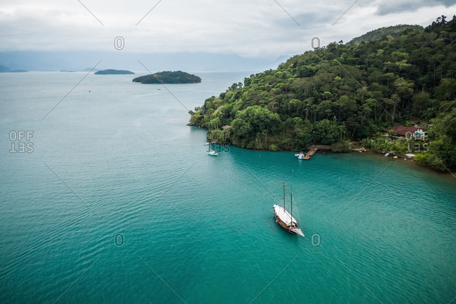 Aerial View Of Sail Boat Anchored In The Turquoise Waters Off The Coast Of Paraty, Rio De Janeiro, Brazil