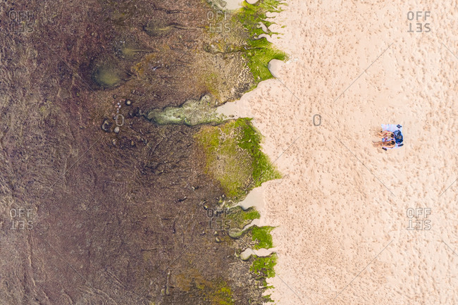 Aerial View Of a A couple laying on beach during low tide on Balangan beach in Bali, Indonesia.