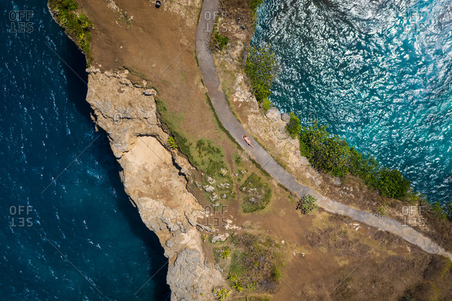 Aerial view of woman laying in dress on path at Broken Beach in Nusa Penida, Indonesia.