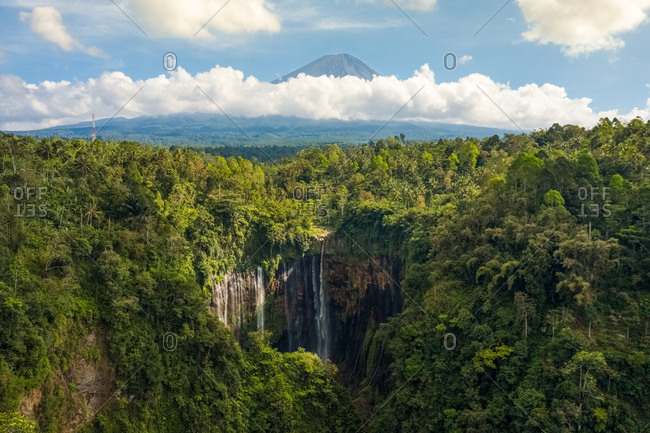 Aerial view of  Tumpak Sewu Waterfall in Java, Indonesia with Semeru Volcano in background.