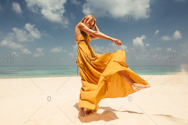 Portrait of a woman in yellow sundress standing on the beach. glamorous woman standing on beach in a long fashionable dress.