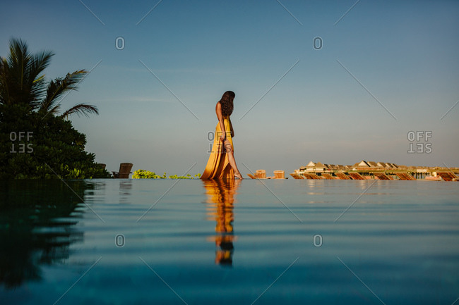 Scenic view of a woman walking at an infinity pool with overwater villas in the background. Woman on a holiday at a tropical beach resort.