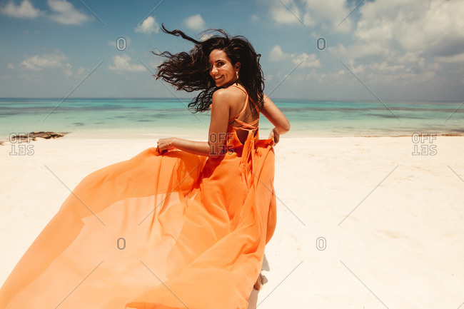 Rear view of a woman running on beach wearing a flowy dress. Smiling woman on a holiday at beach in a fashionable orange sundress.