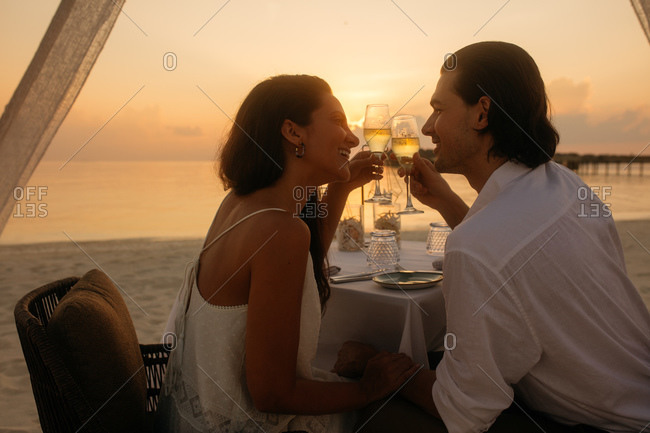 Couple toasting wine glasses sitting at a beach resort. Close up of a couple on a date sitting holding hands drinking wine at sunset.
