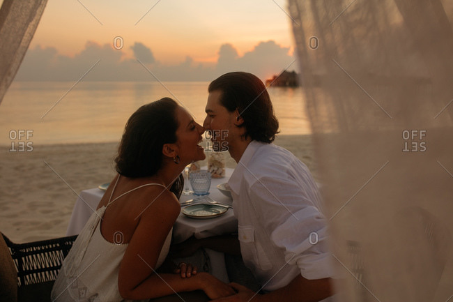 Happy couple celebrating an occasion at a sunset dinner on beach. Couple spending romantic moments touching their nose sitting at a dinner table.
