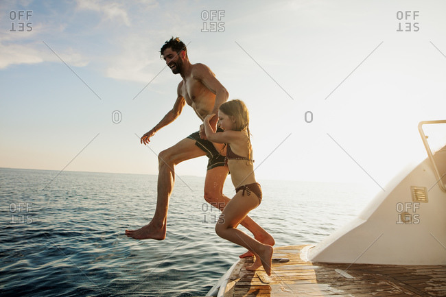 Father and daughter jumping in the sea from a yacht. Father and kid on a vacation enjoying a swim in the middle of the sea.