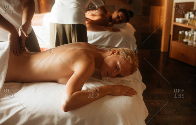 Therapists massaging women at a spa. Woman lying on massage bed and relaxing while a masseuse massages her back.