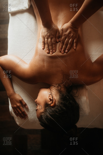Top view of a therapist massaging the back with palms. Woman lying on massage bed experiencing  a relaxing oil massage.