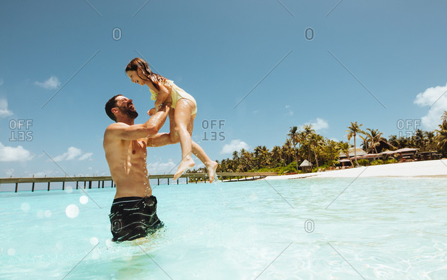 Man playing with daughter in water at a beach resort. Father and daughter enjoying holiday at a tropical beach.