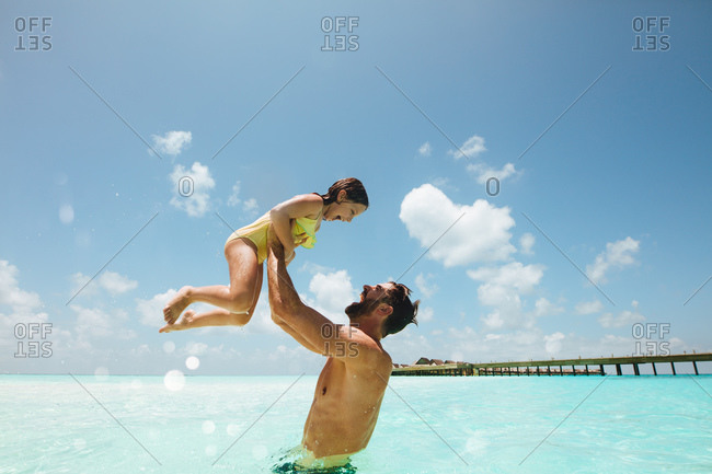 Father and daughter having fun swimming in water. Man lifting his kid enjoying in water at a tropical beach.