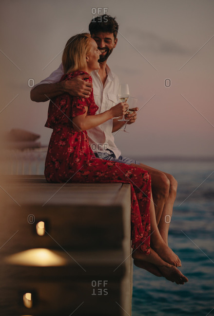 Romantic couple holding wine glasses sitting on an overwater villa. Couple on a vacation enjoying romantic moments and sunset at the sea